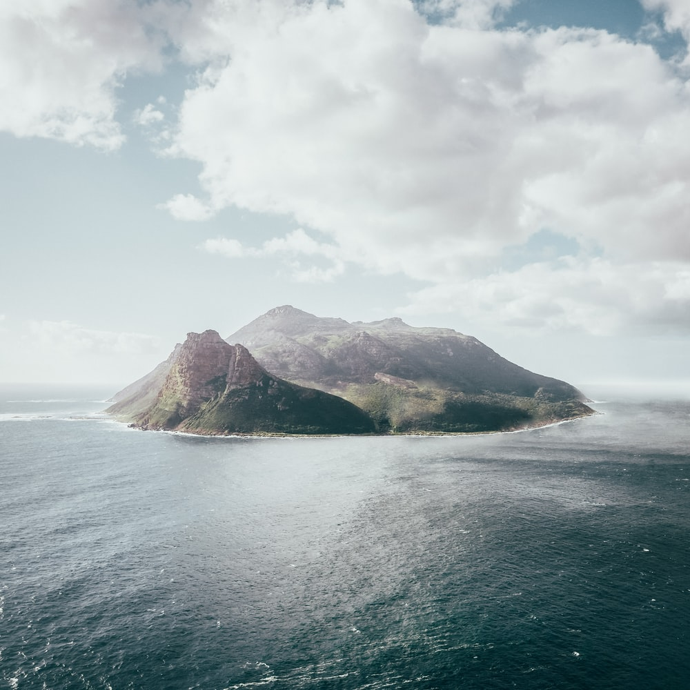 bird's eye view photography of island under white clouds