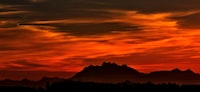 silhouette on mountain during red sky