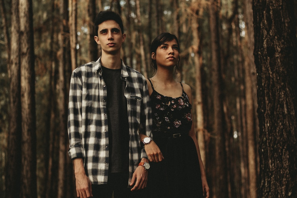 man and woman standing next to another in forest