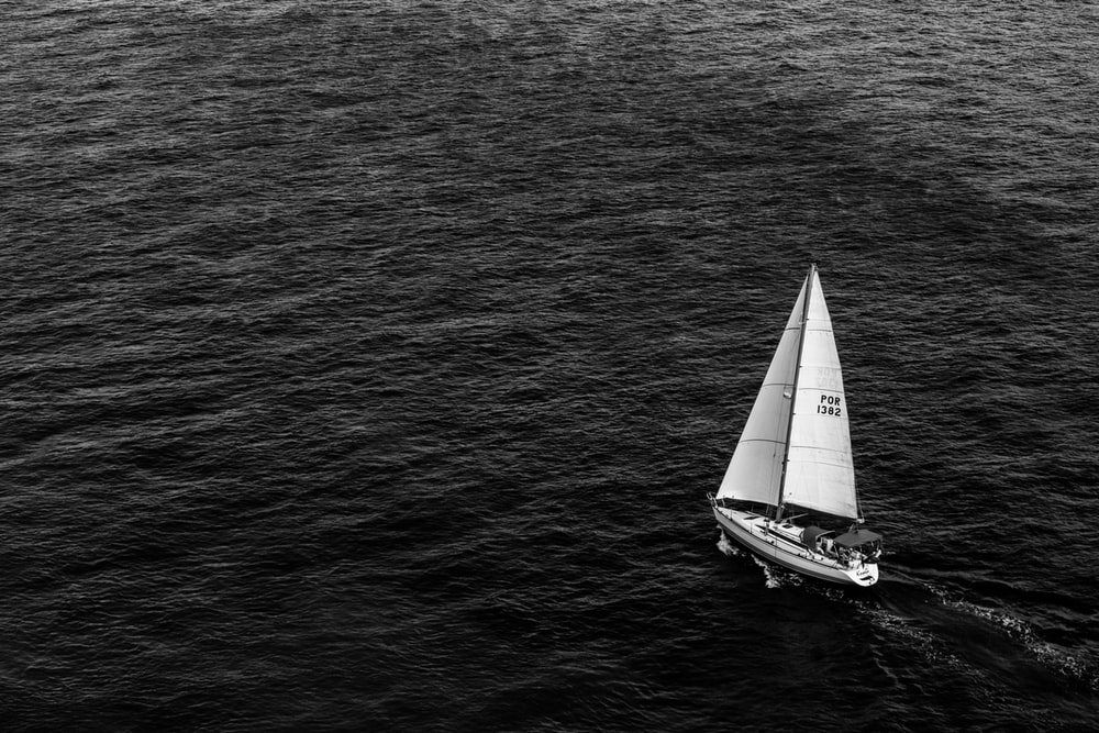 grayscale photography of sailing boat on body of water