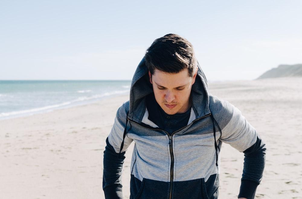 man in gray and black zip-up hoodie walking beside ocean