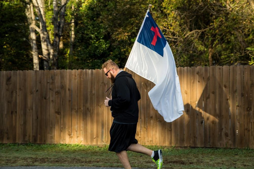 man in black jacket holding flag