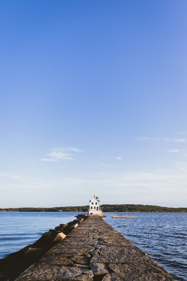 A photo of a small, white cabin at the end of a long peninsula over the water with a big blue sky above and blue water below.