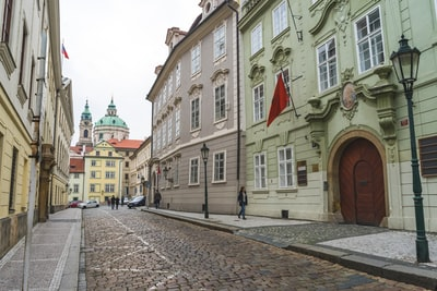 woman walking on street with red flag above her czechia zoom background