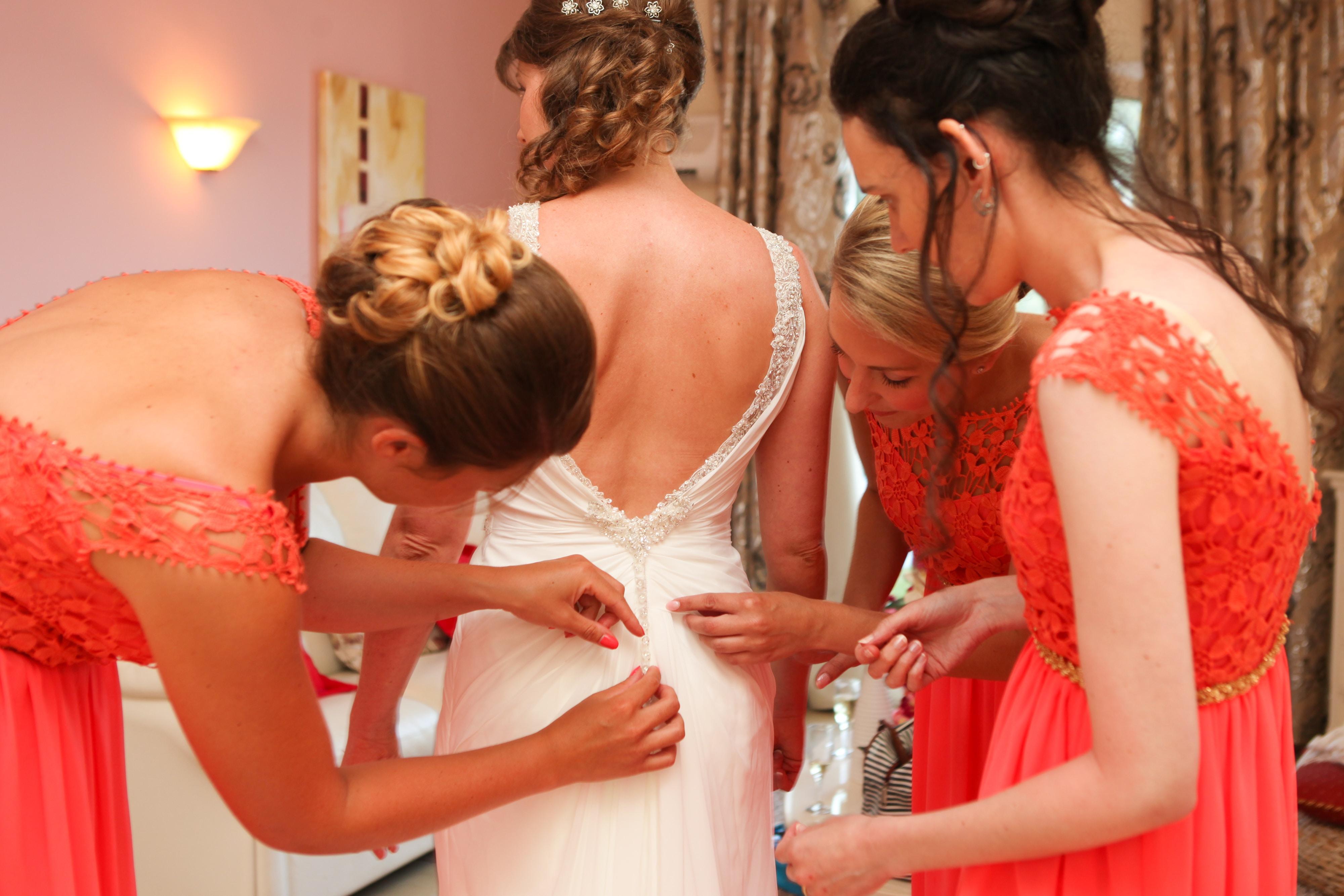 three women's fixing wedding gown