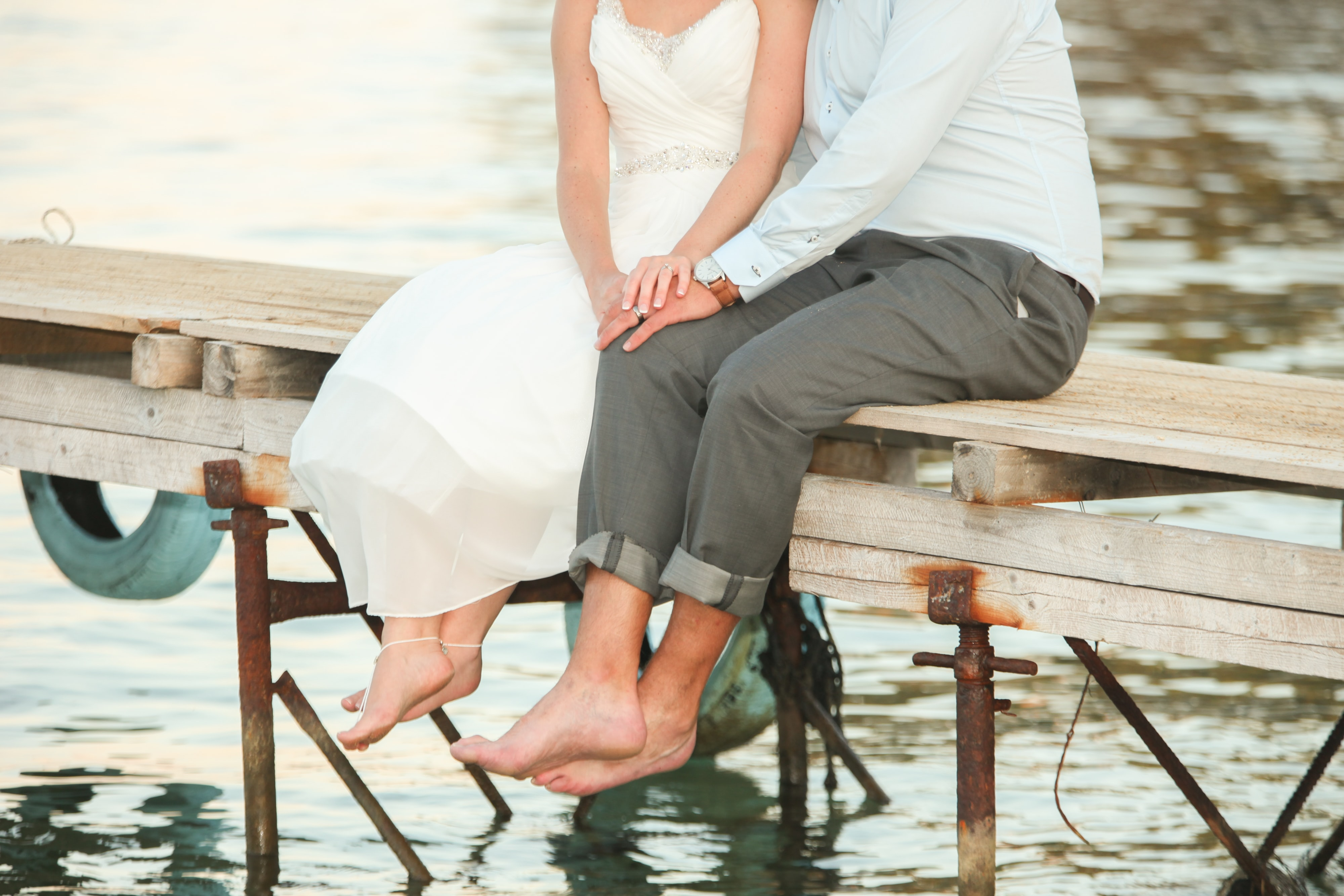 man and woman sitting on dock above water