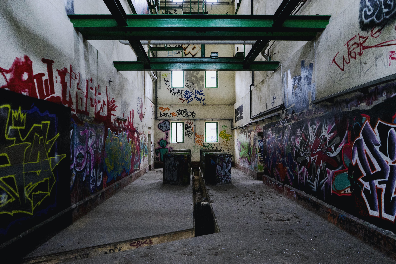 gray narrow pathway in between walls inside building