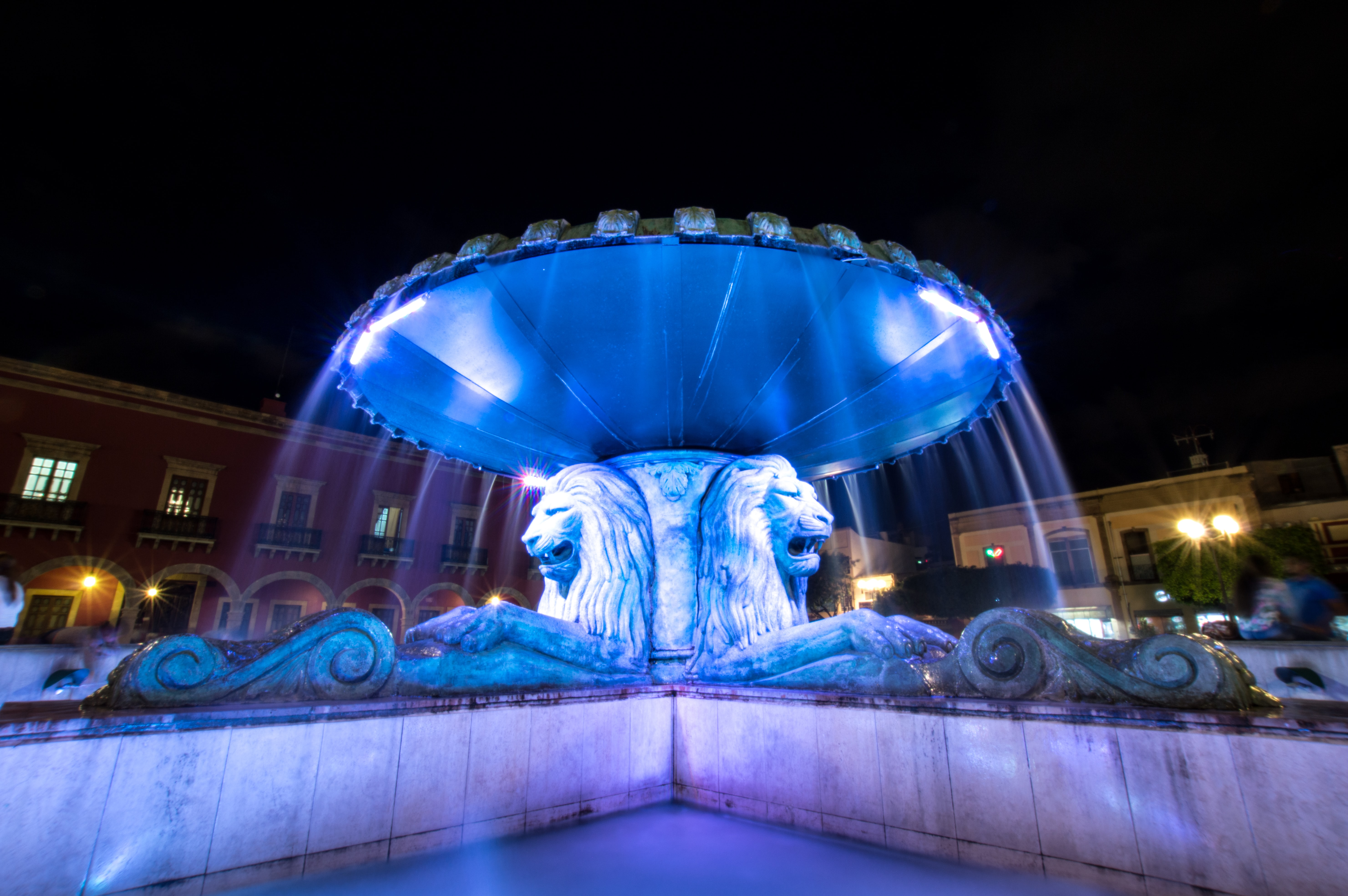 lion fountain with blue light in middle of fountain
