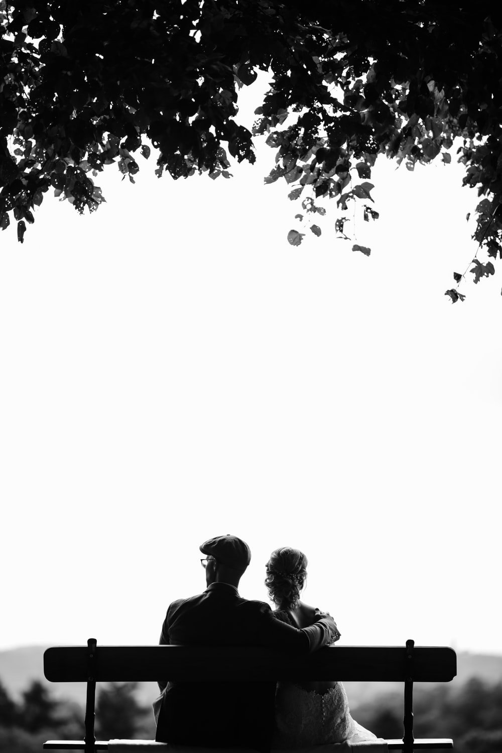 couple sitting on bench under tree grayscale photography
