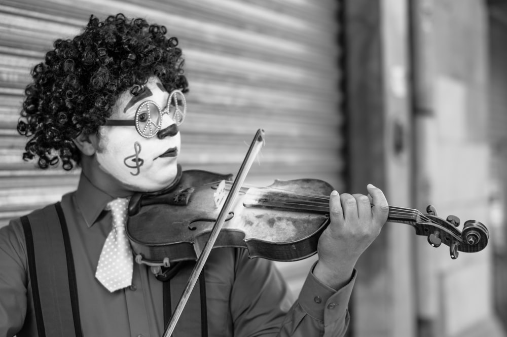 grayscale photo of man playing violin