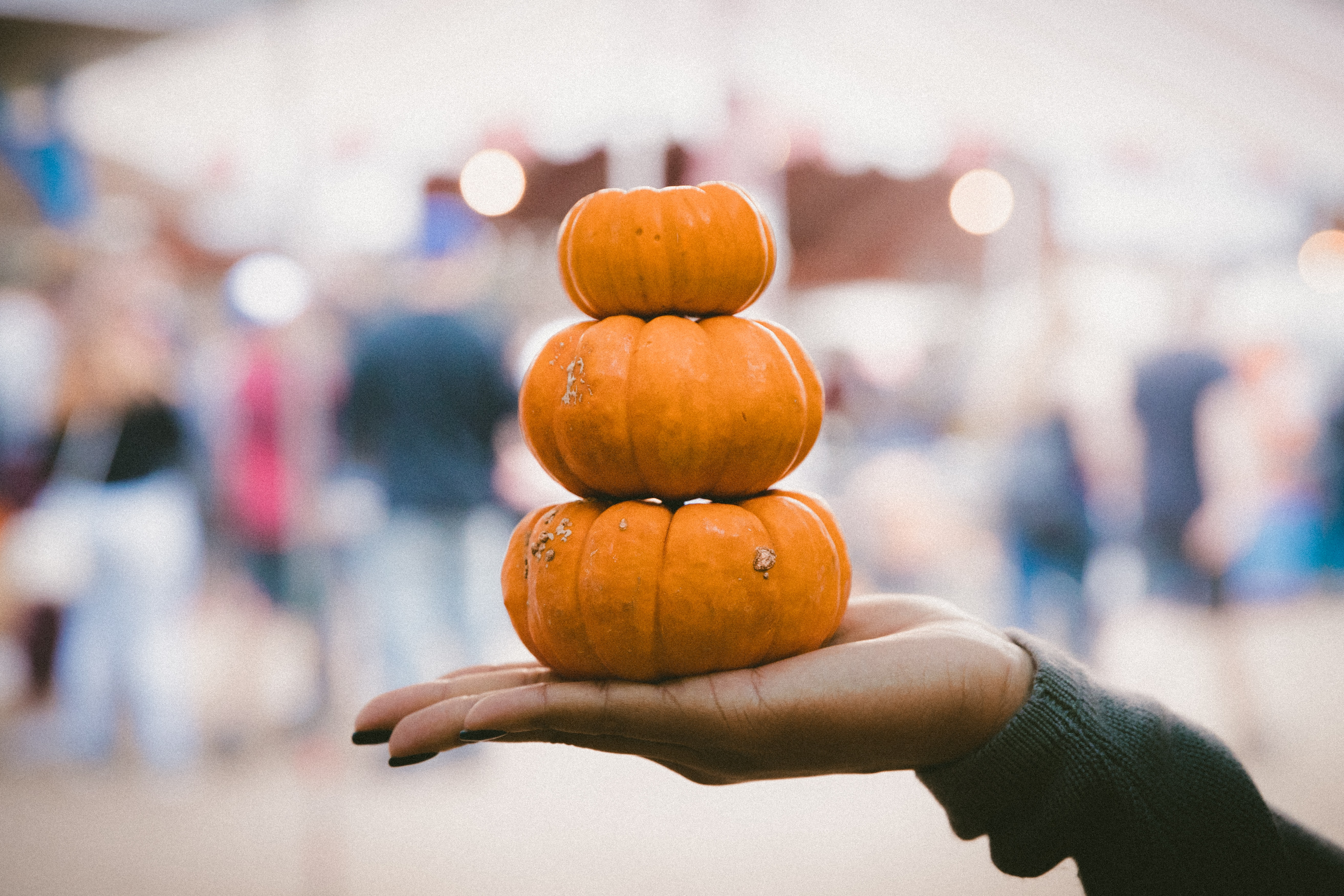 three pile of pumpkins on person's palm
