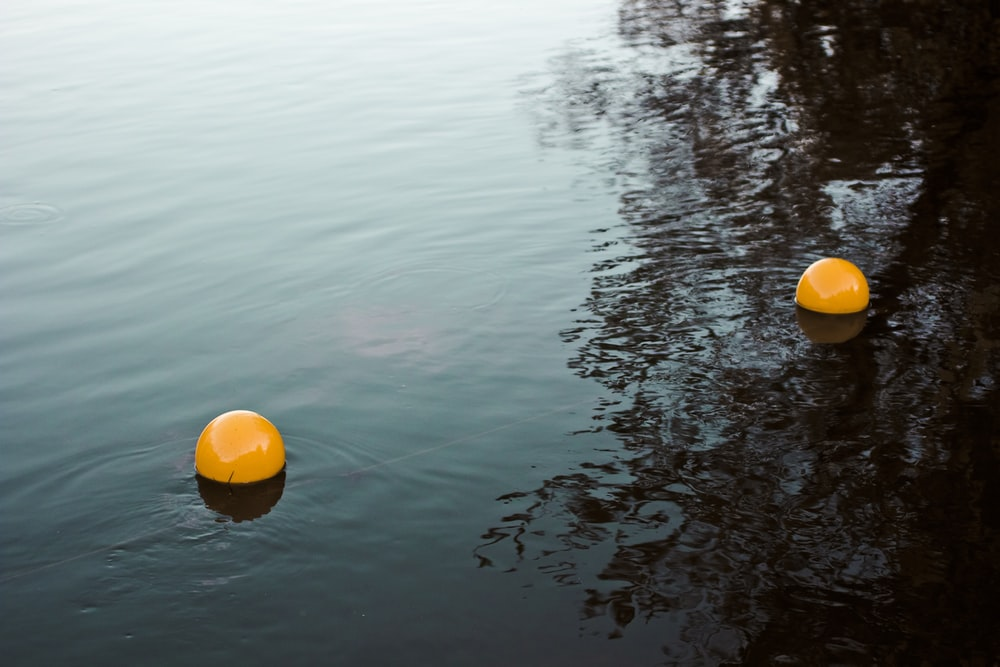 two orange balls on body of water