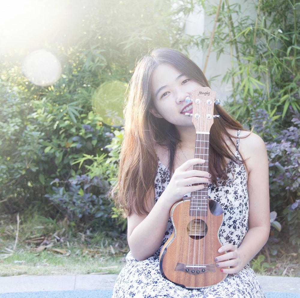 smiling woman holding ukulele near green plants