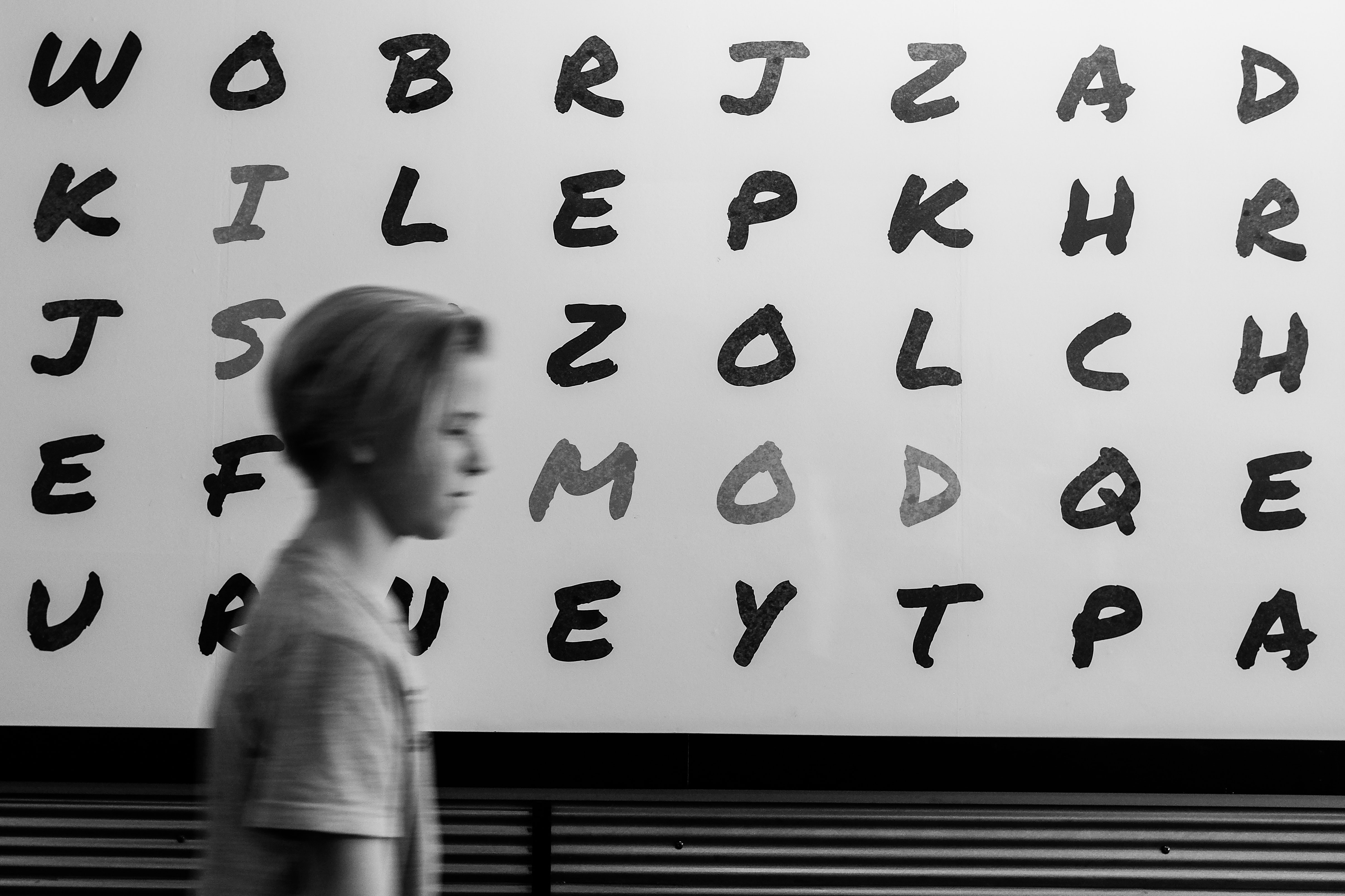 boy standing in alphabet board