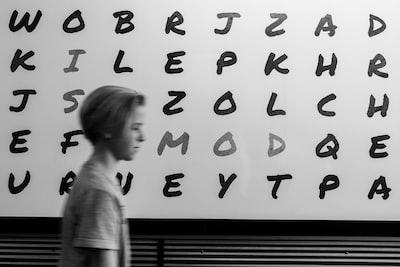 boy standing in alphabet board
