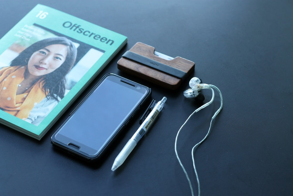 black Android smartphone beside white earbuds, white click pen, and Offscreen book