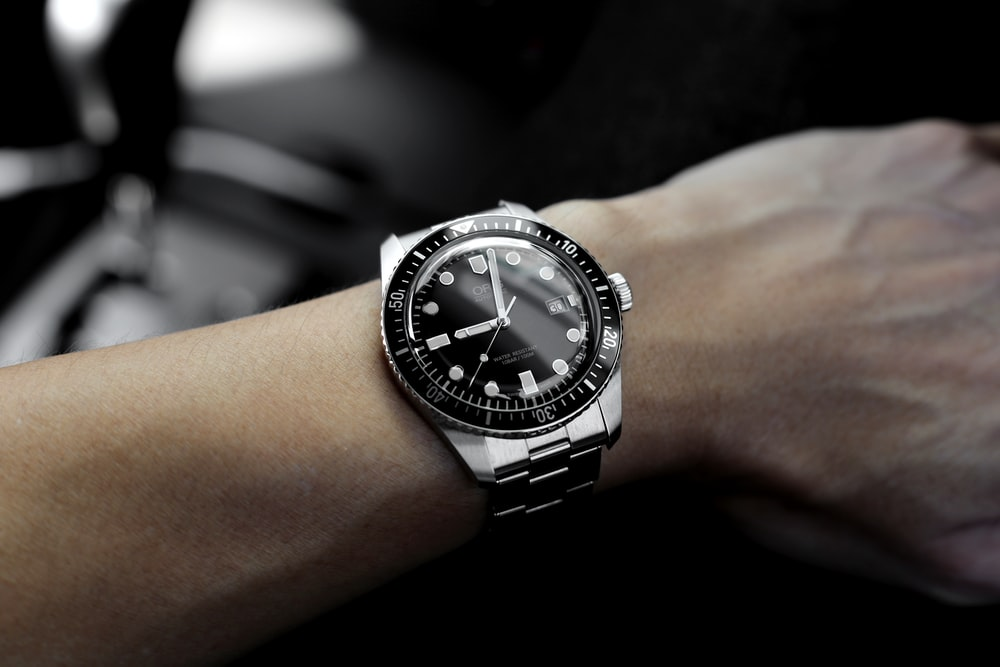 person hand with silver-colored watch