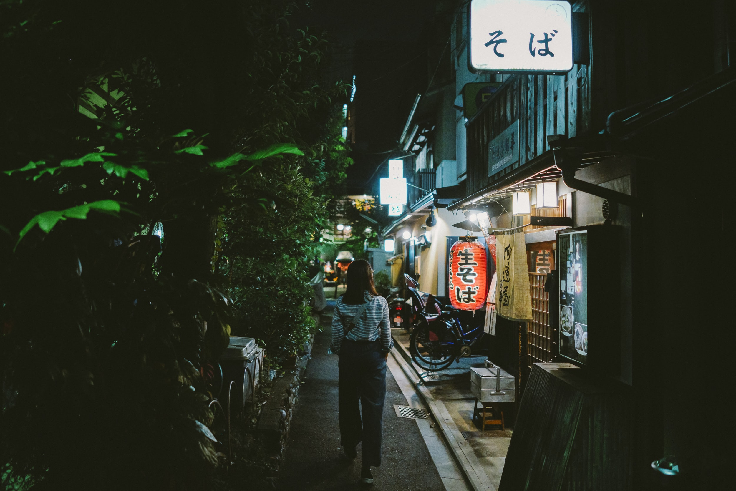 woman walking on pathway at night time
