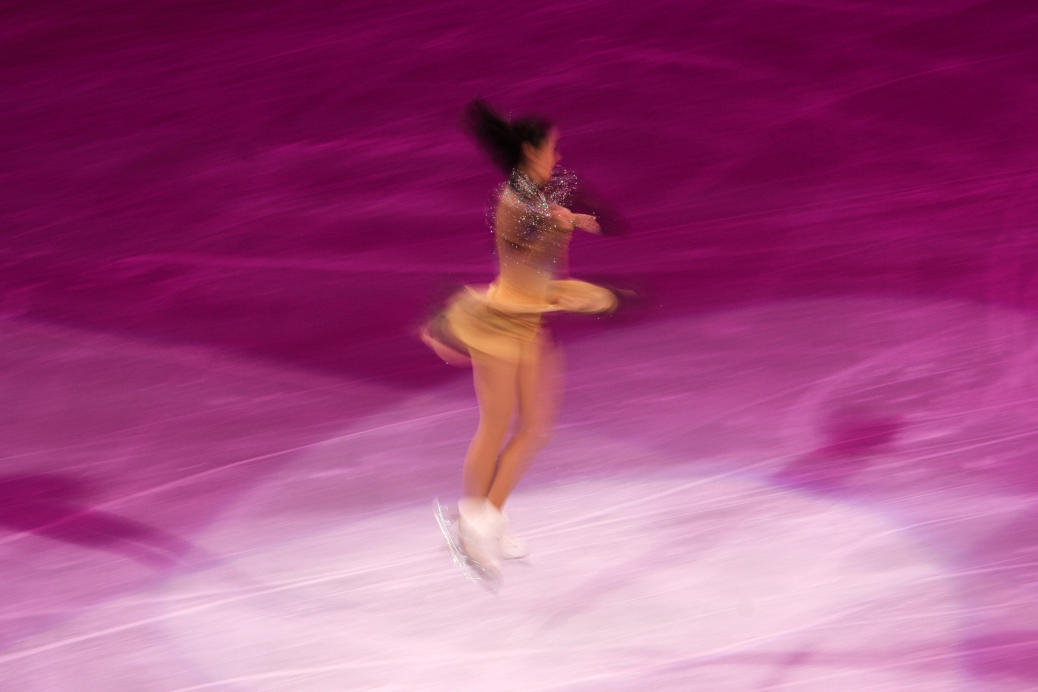 woman in beige performing ice skate