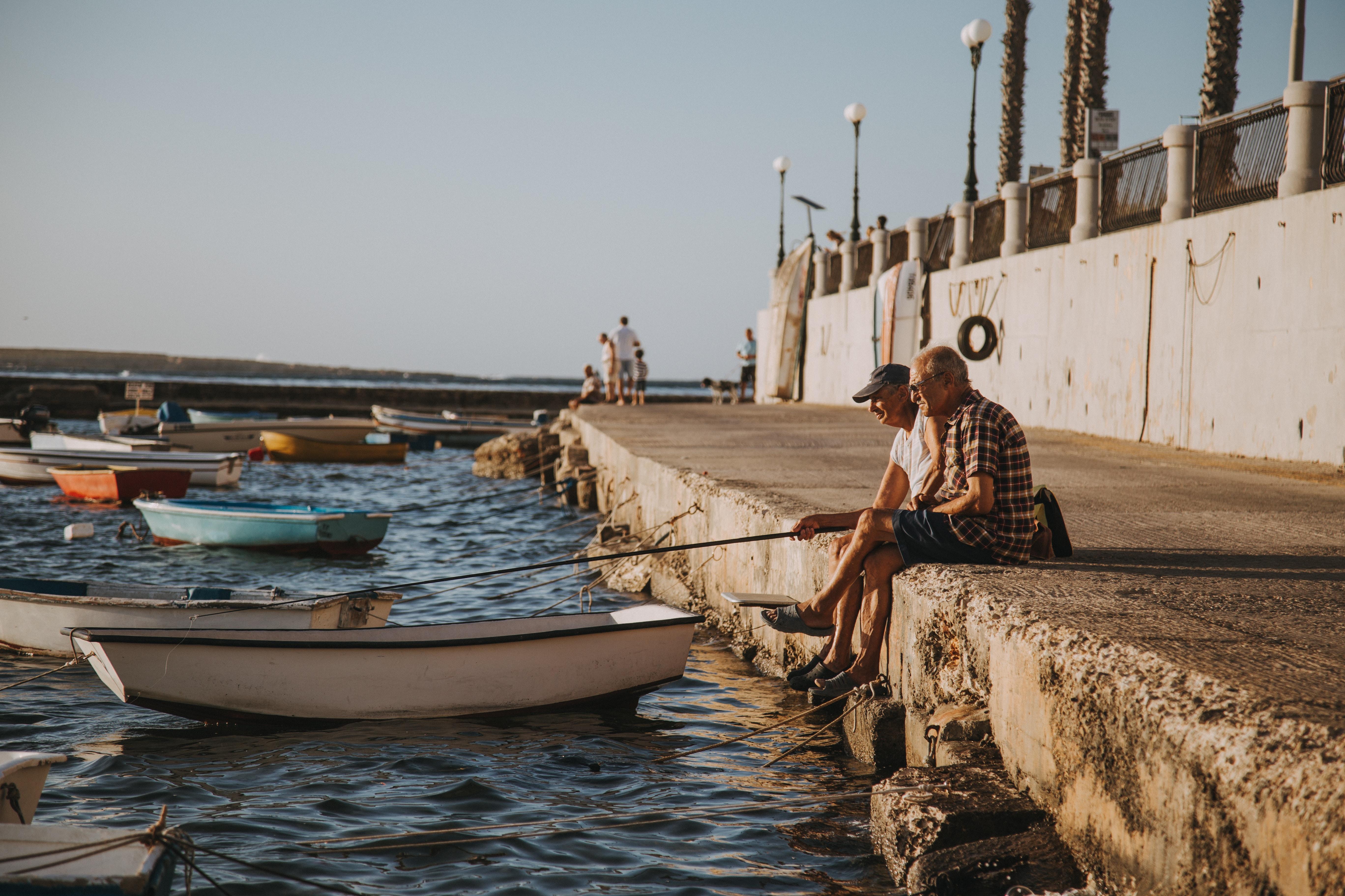 two men fishing near boats