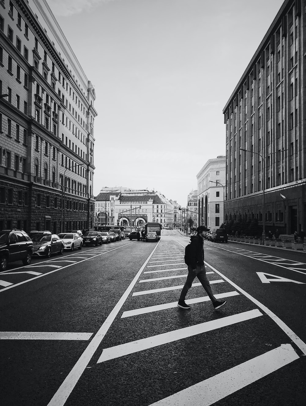 man walking on the street between high-rise building