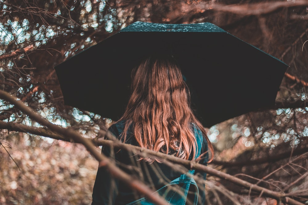 woman standing while holding black umbrella