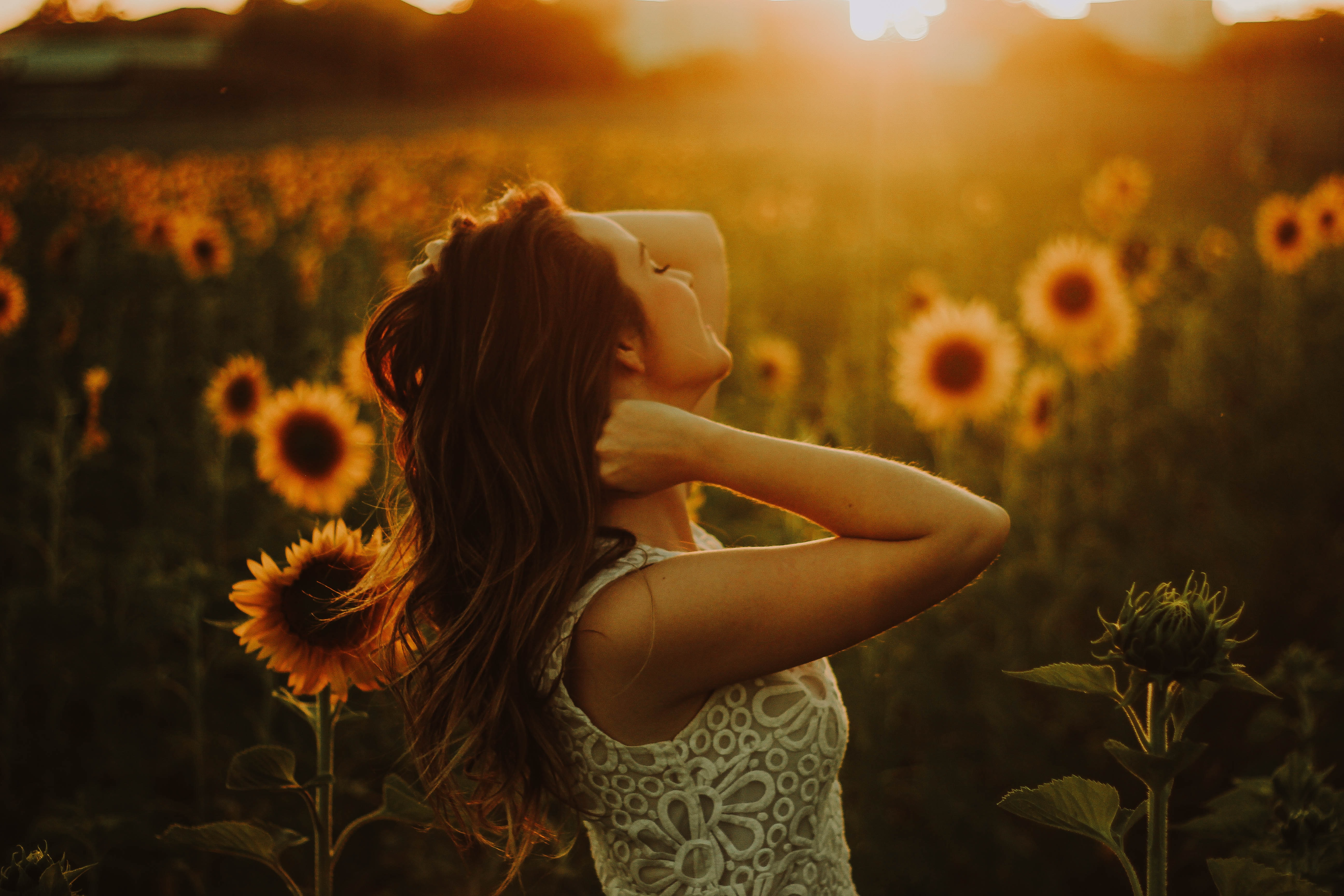 woman standing near sunflower field
