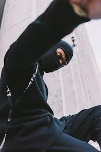 man wearing black mask, black long-sleeved shirt, and black pants sitting near wall