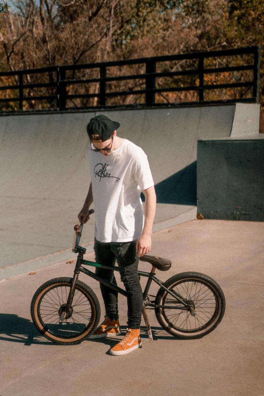 man about to ride on a black BMX bike