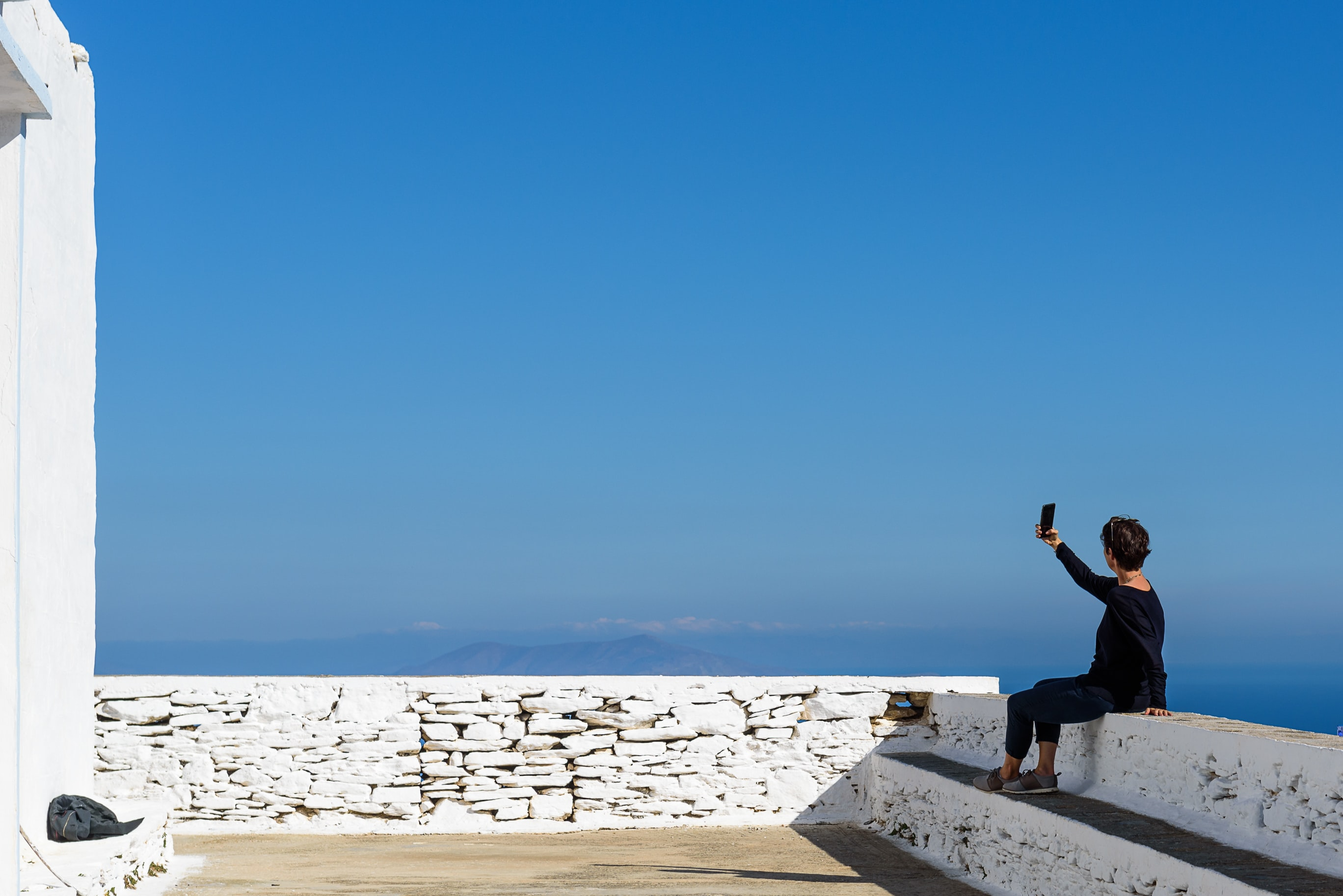 photo of person holding smartphone while sitting on terrace