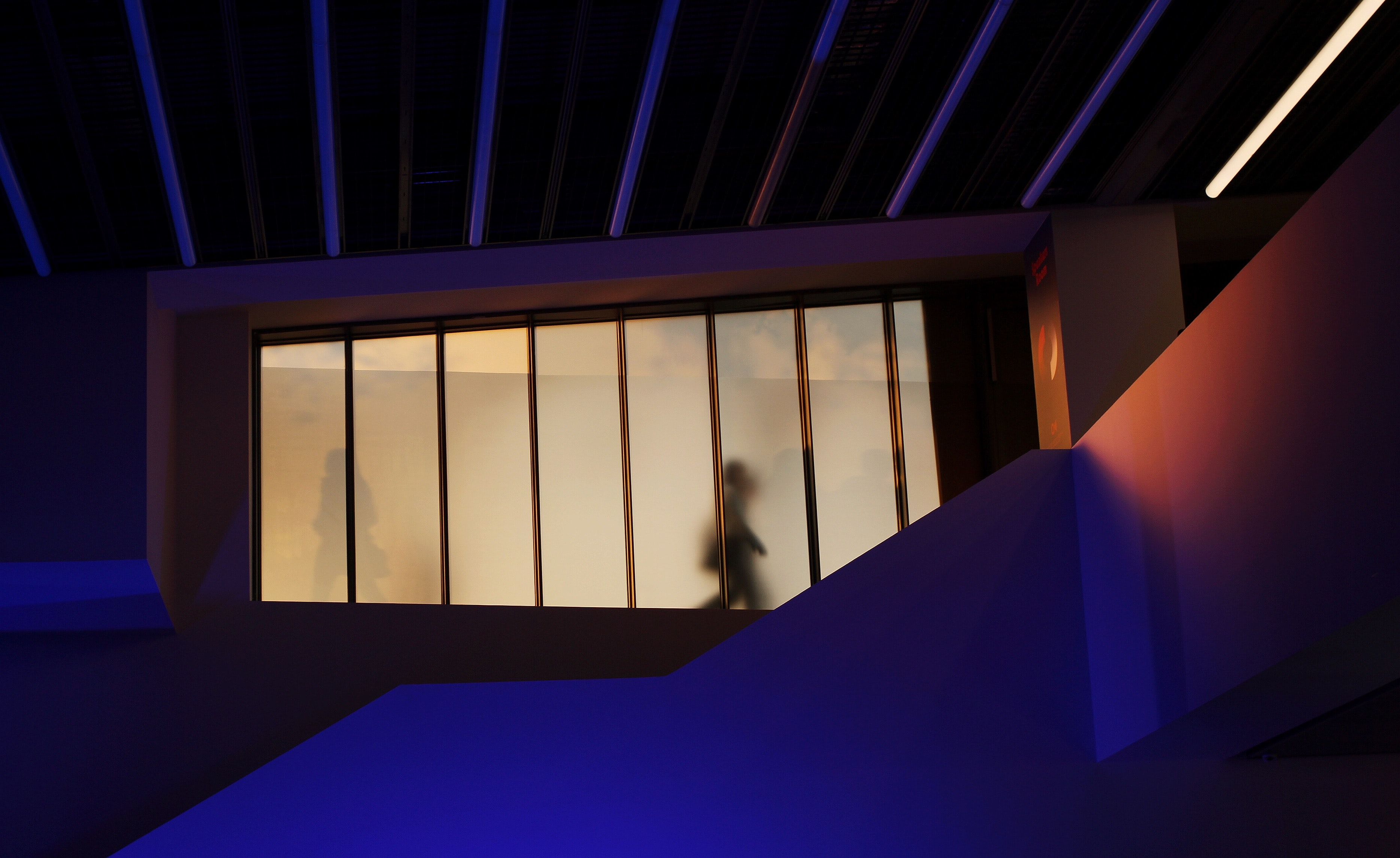 silhouette of two person beyond glass walking on pathway