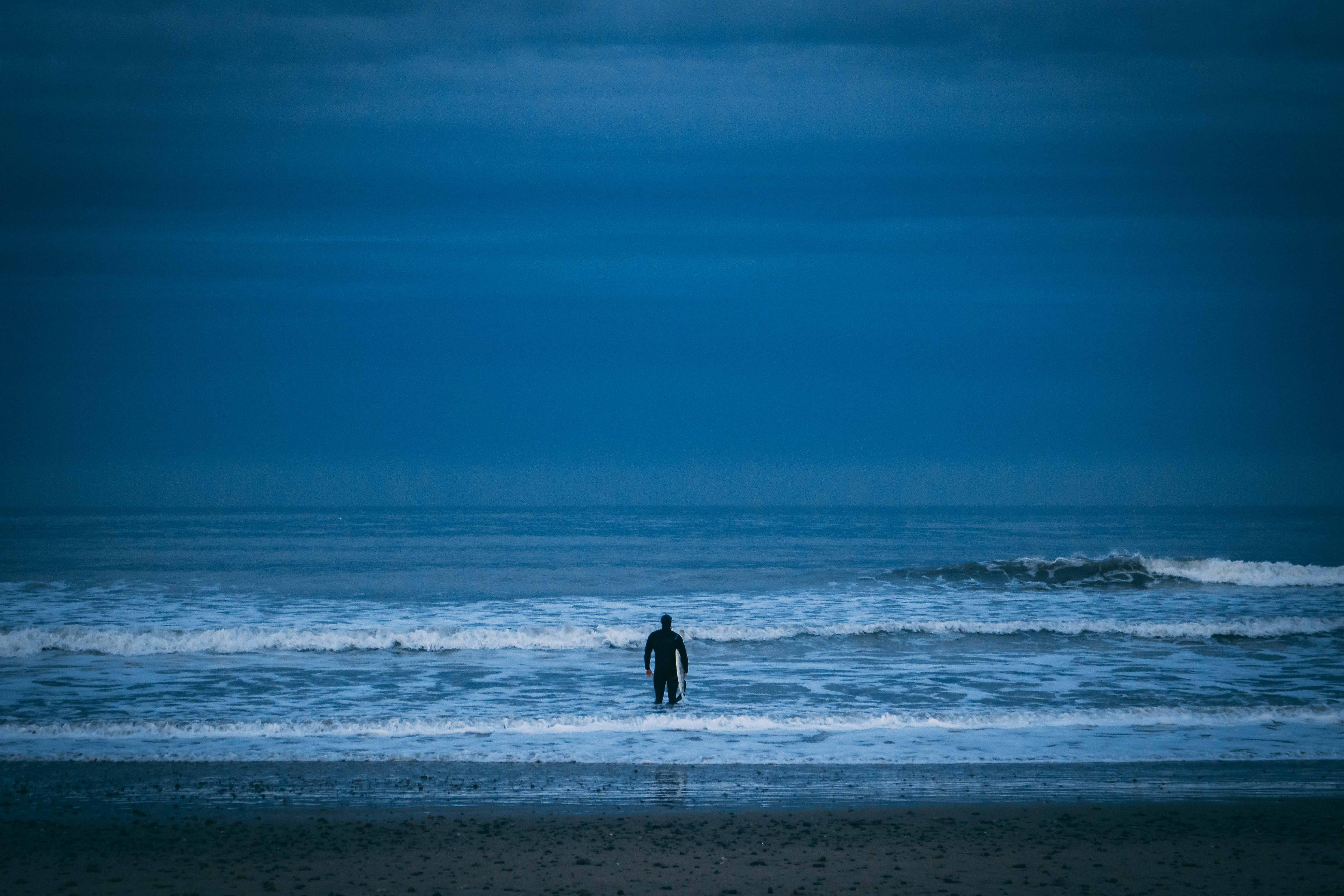 man standing on beach under cloudy sky