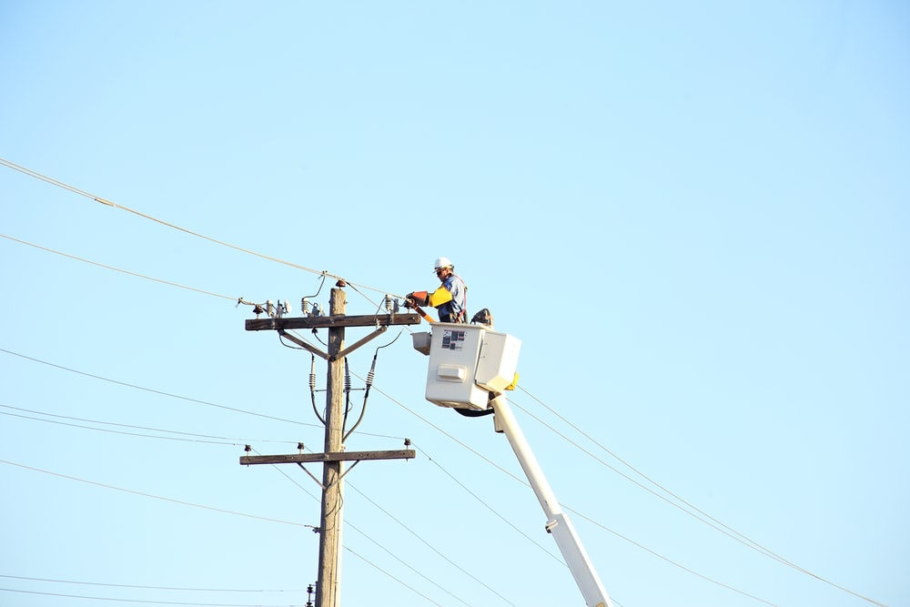 man standing on bucket beside gray current post at daytime