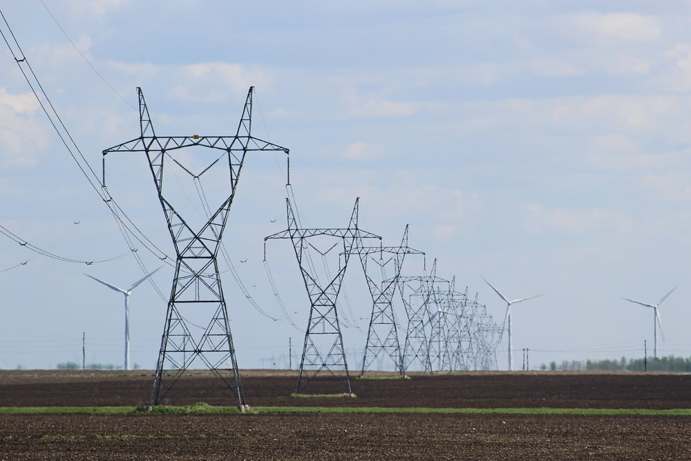 transmission towers and wind turbines on the field