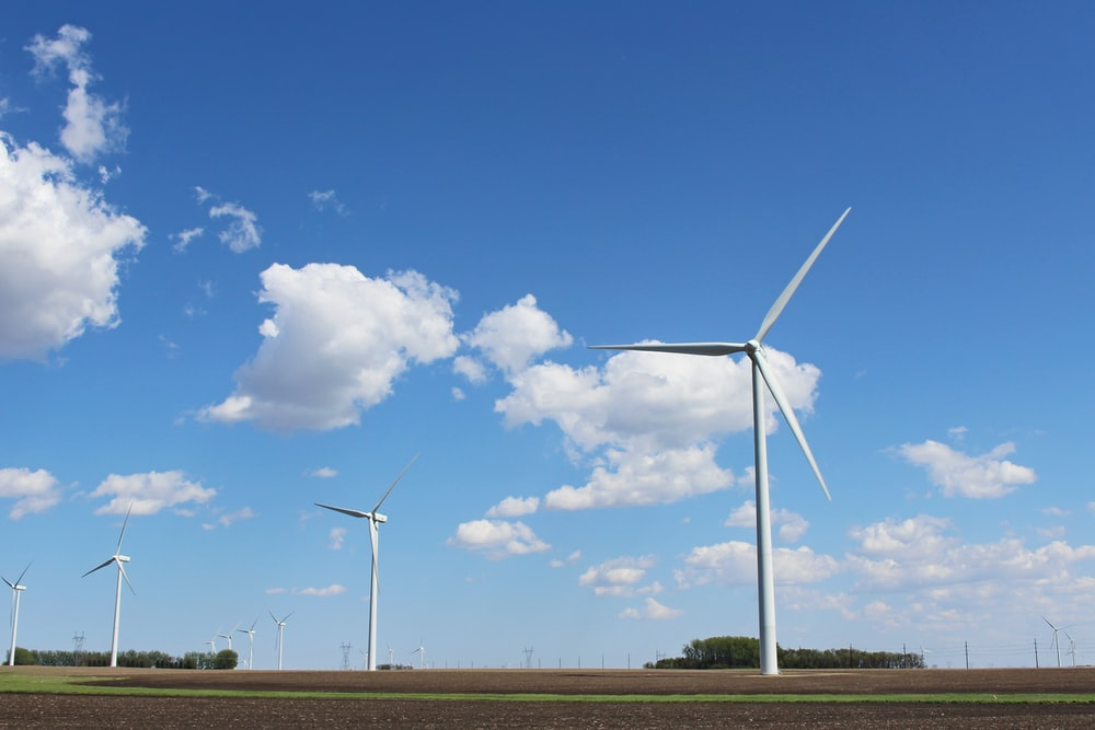 white wind turbines under blue sky during daytime