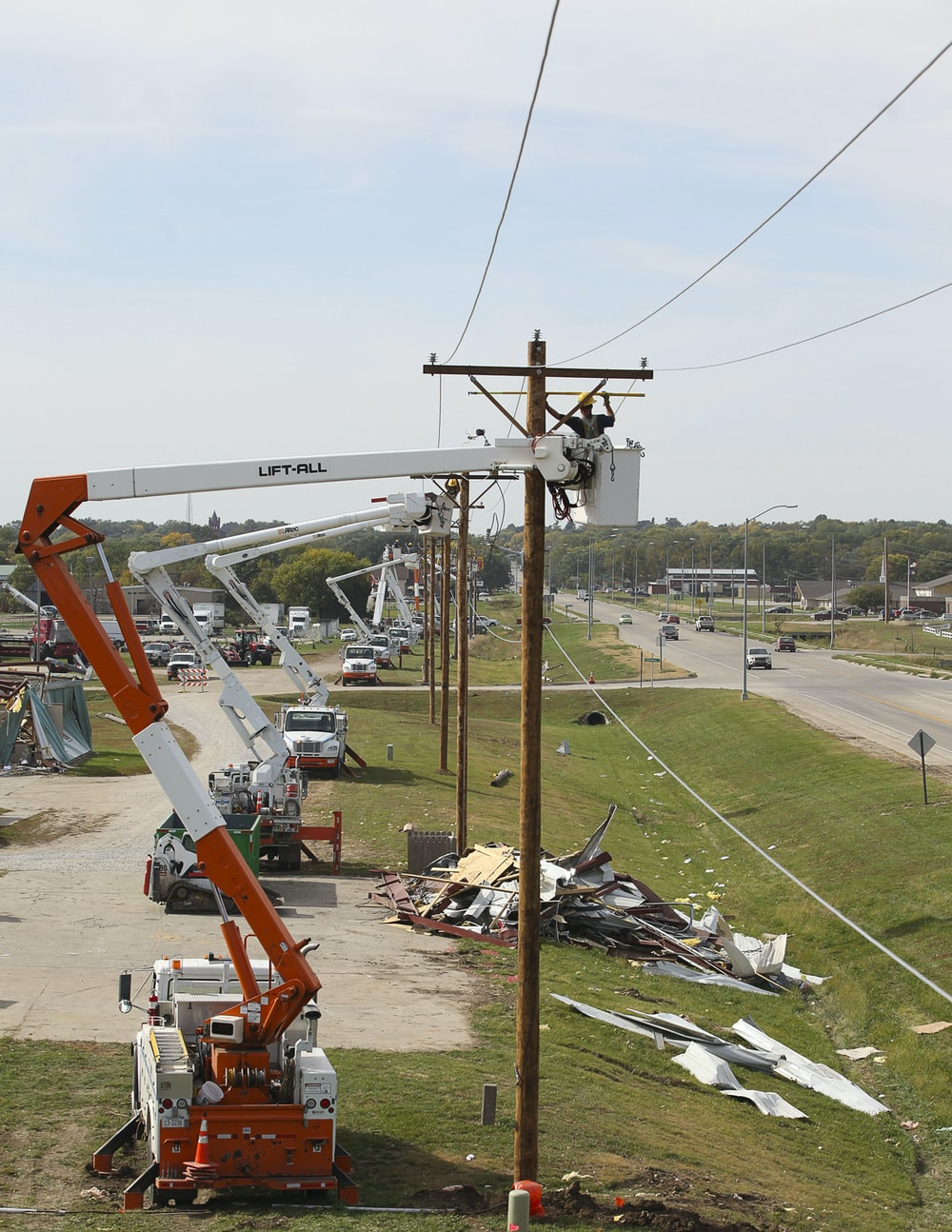 person on bucket crane truck beside utility pole during daytime