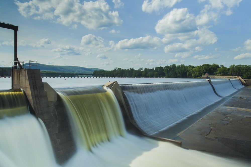 water dam under white and blue skies