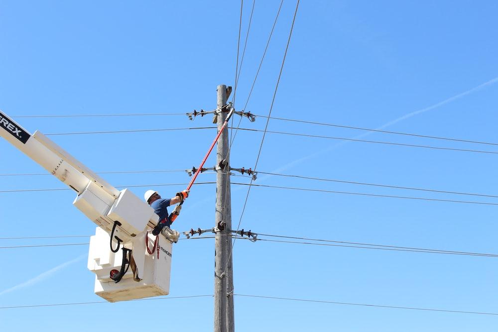 man holding stick near on transmission tower