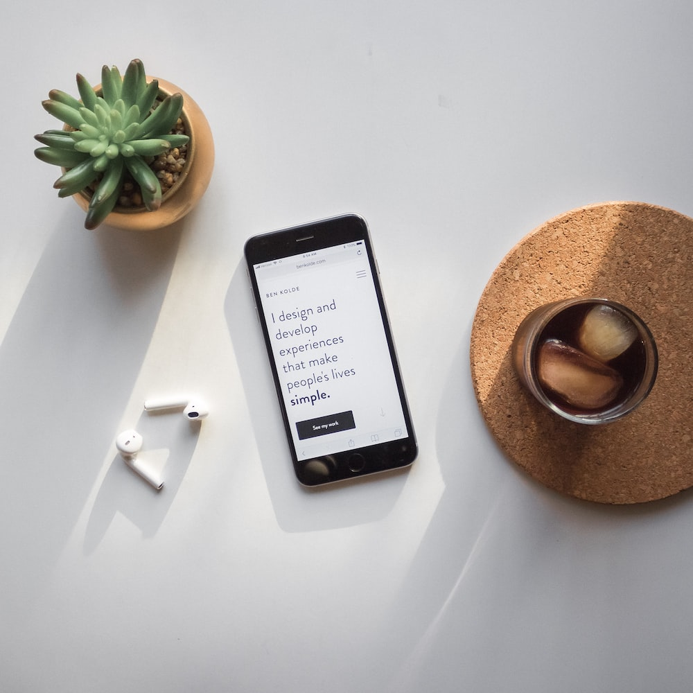 post-2014 iPhone beside Apple AirPods and succulent plant on white surface
