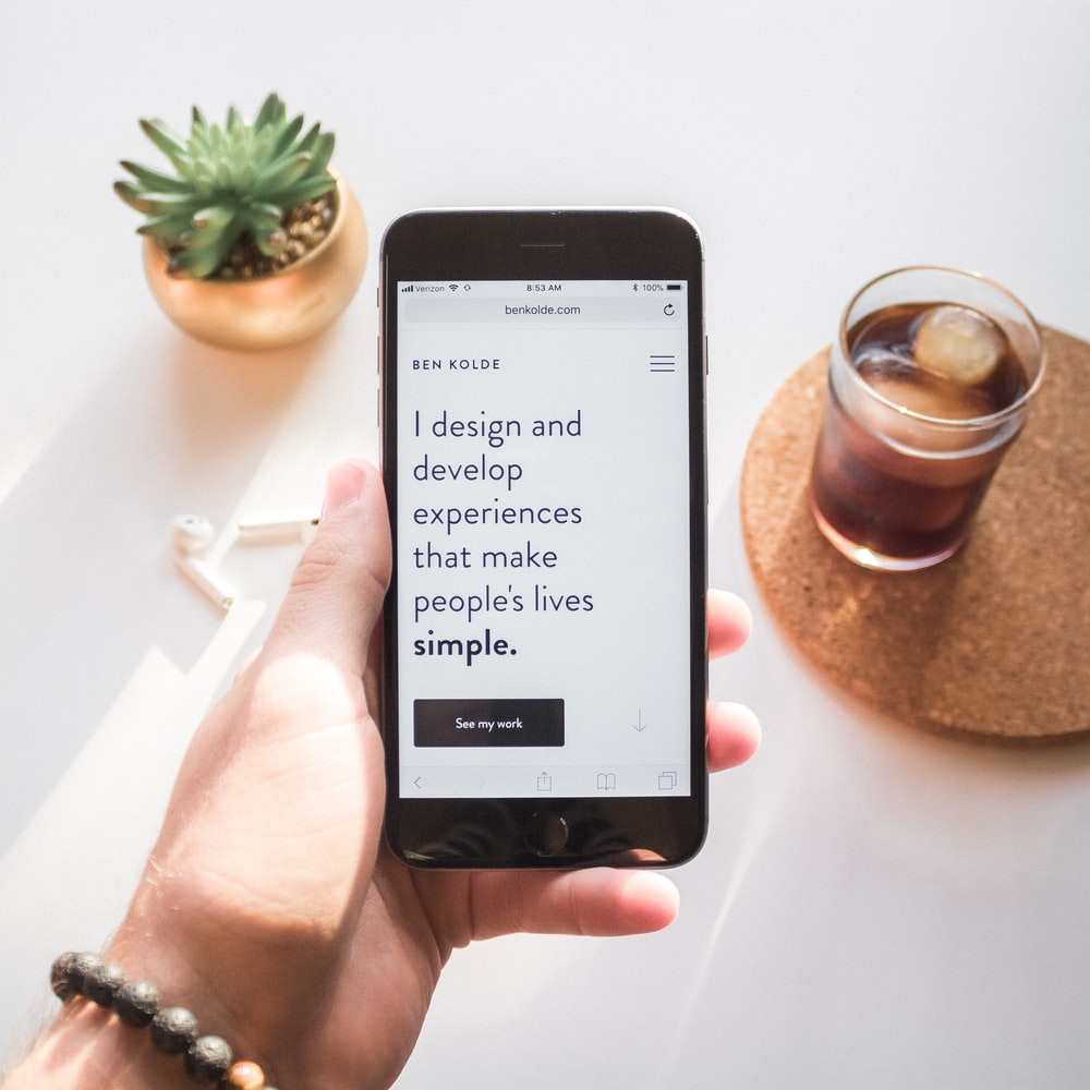 person holding space gray iPhone 6 displaying i design and develop experiences that make people's lives simple text