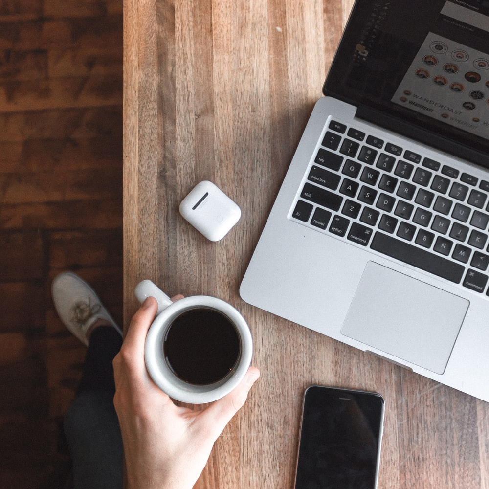 person holding cup of coffee beside gray laptop computer