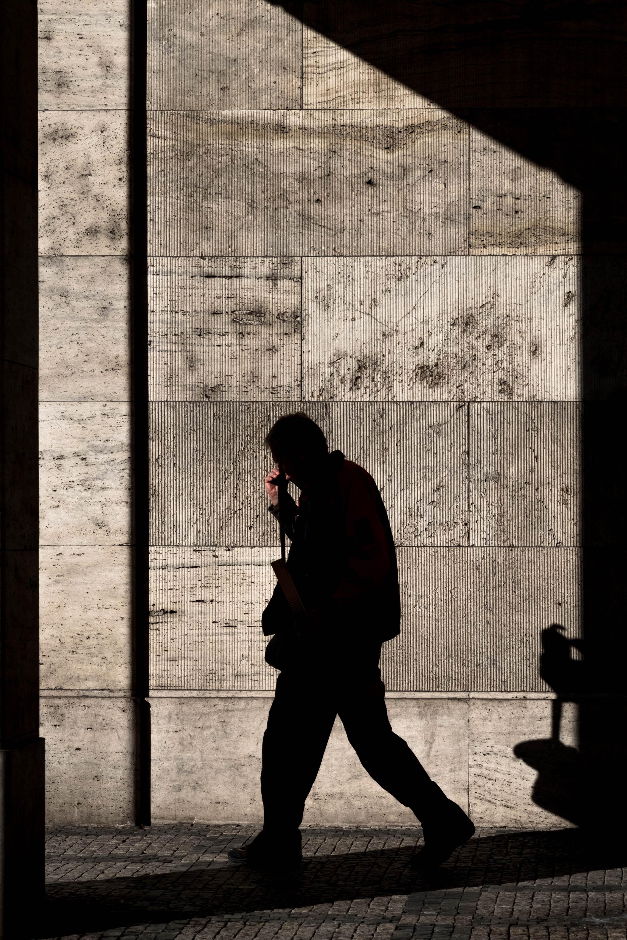 shadow of man walking near wall