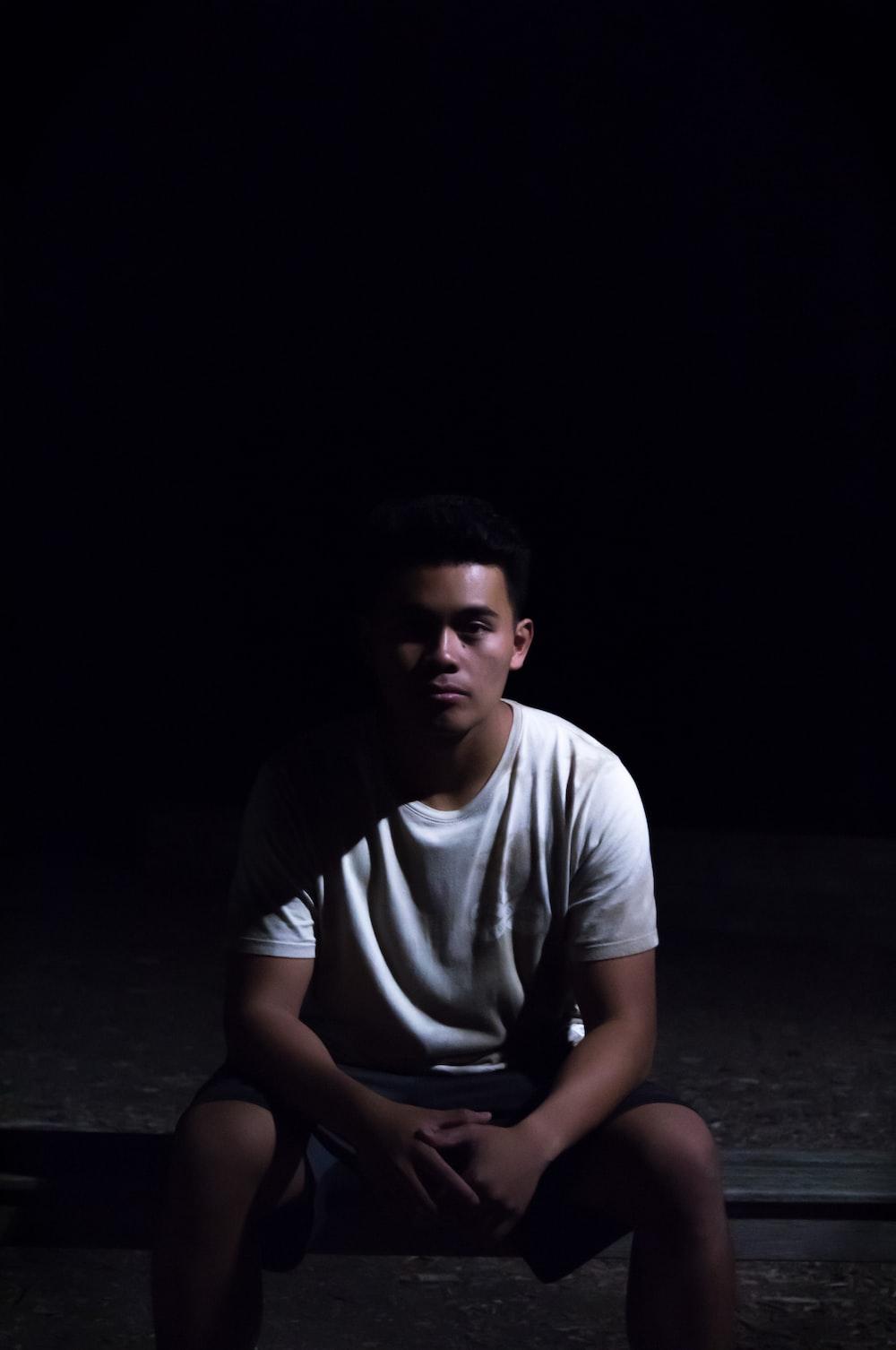 man sitting on ground with black background