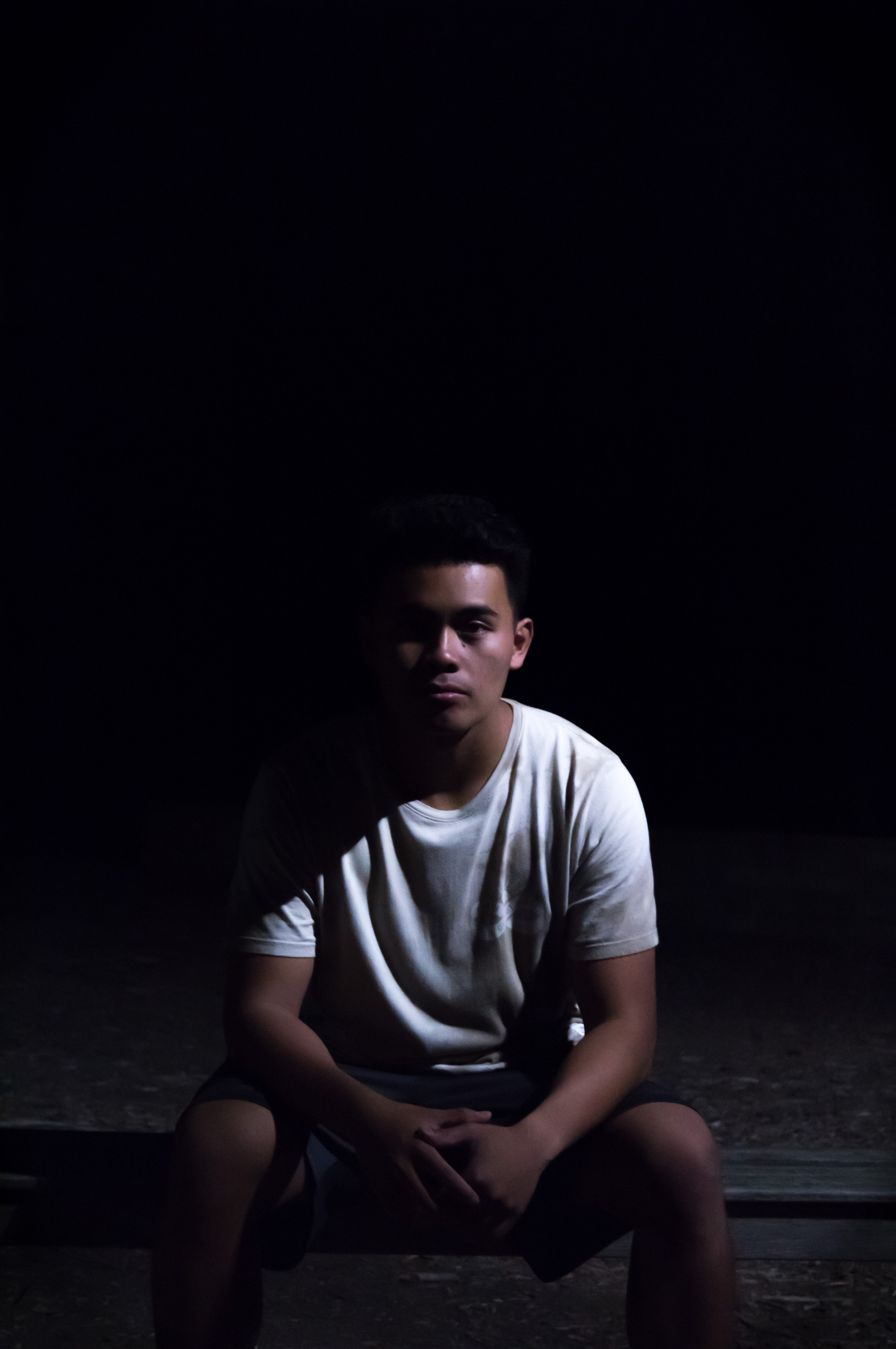 man sitting on ground with black background
