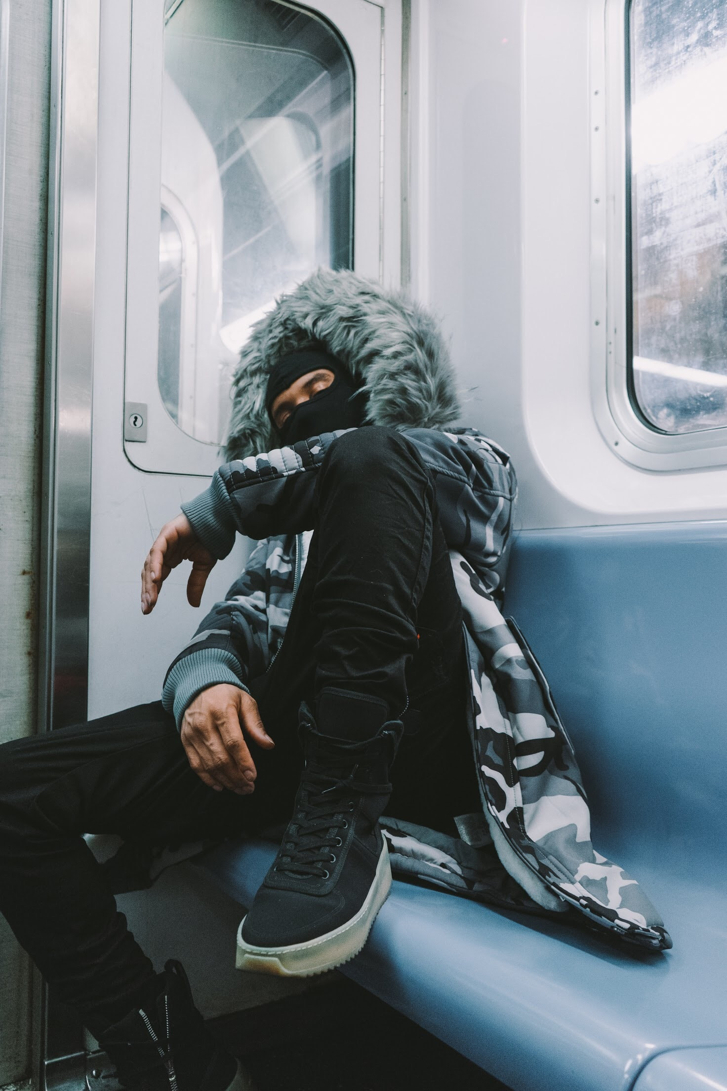 man sitting while leaning on the corner of passenger train wearing fur jacket