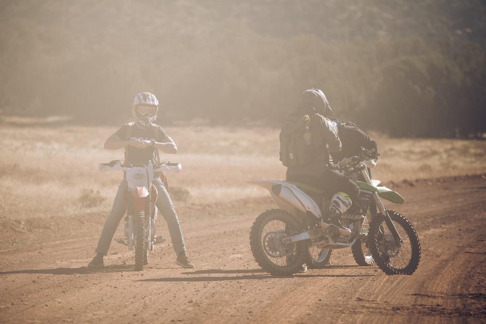 three men in motocross dirt bikes on road