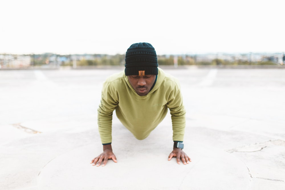 man in green long-sleeved shirt doing a push-up on gray concrete pavement