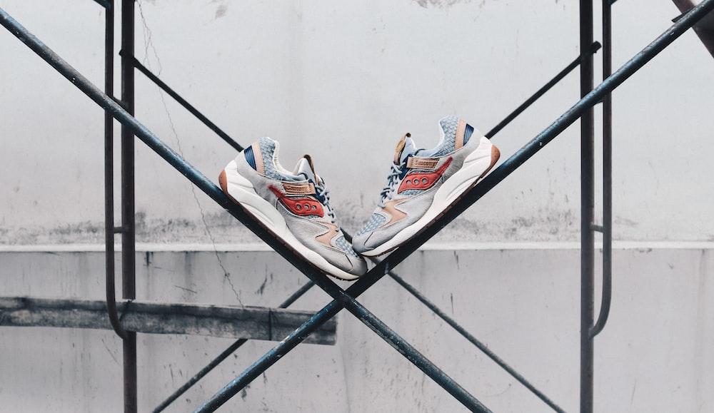 pair of gray sneakers on black steel frame