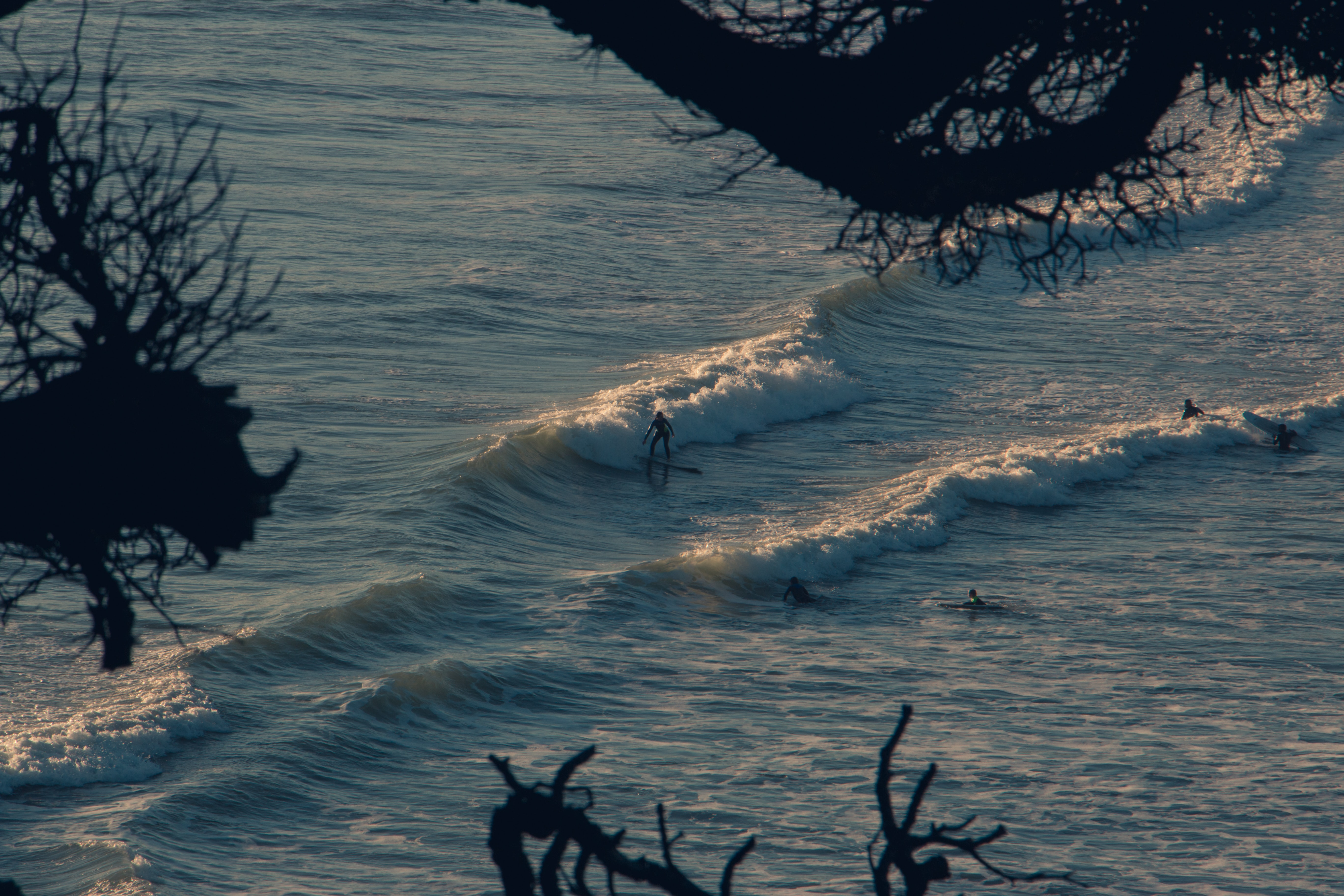 person riding surfboard on body of water