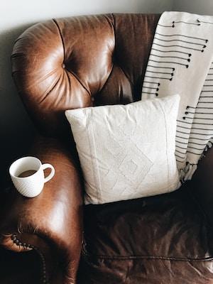 Fåtölj med kuddar och kaffekopp